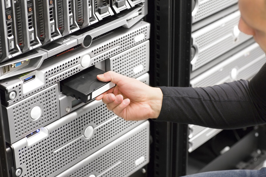 It engineer or consultant working with backup server in racks. Shot in data center.